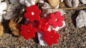 Röda legoblommor på en sandstrand.
