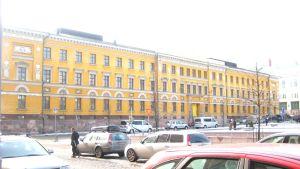 En gul stor byggnad på andra sidan ett torg. Det ligger snö på marken. Bilar står parkerade på gatan framför byggnaden.