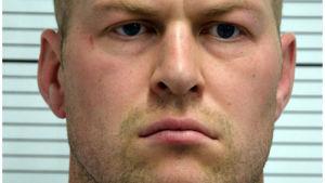 En polisbild på en snaggad man med bryskt ansiktsuttryck.