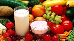 Stilleben av frukt, grönsaker och upphälld sojamjölk och vasslekvarg.
