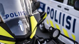 Poliisi mönkijä poliisi auton edessä