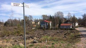 Ett uthugget nytt markområde med äldre hus i bakgrunden.