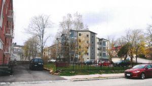 Ett grått flervåningshus i fyra våningar har ritats in på en tomt med gräsmatta och bilar parkerade omkring.