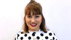 En leende kvinna står vänd rakt mot kameran. Hon har en blus med bollar på och hennes hår är uppsatt i en tofs.