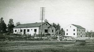 Svartvit bild från 1940-talet av vita byggnader ursprungligen byggda för skyddskårens stab.