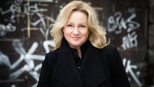Teaterchefen Maria Sid mot en bakgrund med vit text på svart vägg.