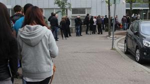 Människor köar utanför polisstationen i Böle, Helsingfors.