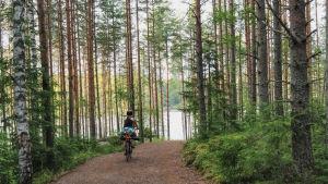 En kvinna cyklar på en cykel som har mycket packning på pakethållaren. Hon cyklar i en skog och framför henne finns en sjö.