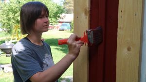 Katrine Jensen målar en vägg.
