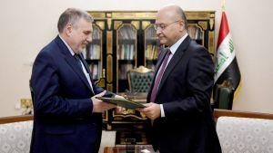 Iraks president Barham Salih (till höger) utser Mohammad Allawi (till vänster) till Iraks nya premiärminister. På bilden står männen framför en bokhylla och Iraks flagga.