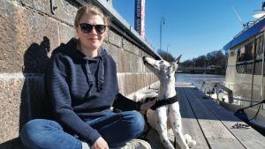 En ung kvinna med solglasögon sitter på en brygga med en hund bredvid sig som tittar på henne.