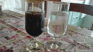 Två glas med vatten, varav det ena har svart vatten.