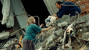 En kvinna får hjälp med att hitta sina kläder i bråte efter jordbävning i Izmit