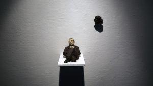 En staty på en liggande man mot en vit vägg.