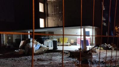 Byggarbetsplats i mörker fotad bakom ett stängsel.