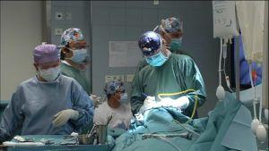 Personer i ljusblå skyddsutrustning genomför en operation.