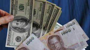 Yhdysvaltain dollareita ja Thaimaan bahteja.