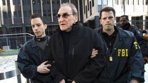 Harmaa hiuksinen mies käsiraudoissa kahden miehen taluttamana, toisen takissa lukee FBI.