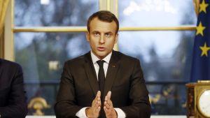 Ranskan presidentti Emmanuel Macron istuu pöydän ääressä.