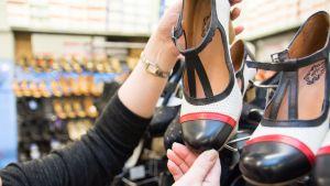 Myyjä esittelee kenkäkaupan hyllyssä olevaa korkokenkää.