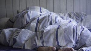 Henkilö lepää sängyssä peiton alla.