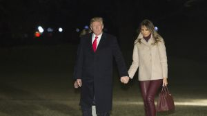 Yhdysvaltain presidentti Donald Trump ja Melania Trump kävelevät käsikädessä nurmikolla.