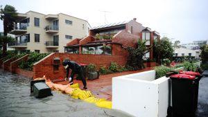 Asukas kasasi hiekkasäkkejä estääkseen veden nousemista Aucklandissa 5. tammikuuta.