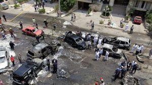 Autopommi on räjähtänyt kadulla. Useita autoja on tuhoutunut ja ihmisiä katselee ympärillä.