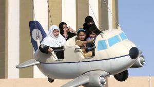 Saudiperhe huvipuistolaitteessa. Naisilla on huivit päässä.