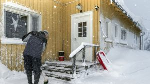 Mies lakaisee lunta pois talon portailta Hyrynsalmella.