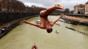 Marco Fois sukeltaa Tiber-jokeen perinteisessä uudenvuoden hyppytilaisuudessa Roomassa.