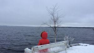 Tyttö istuu jäisellä puistonpenkillä Näsijärven rannalla.