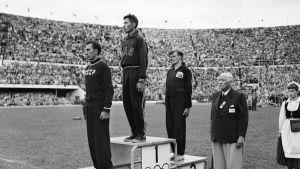 Helsingin olympialaisten estejuoksun voittajat, ylinnä Yhdysvaltojen Horace Ashenfelter, edessä Neuvostoliiton Vladimir Kazantsev ja kolmantena Iso-Britannian John Disley kuuntelevat mitalikotelot kädessä 'Star-Spangled Banner'ia. Oikealla Kansainvälisen olympiakomitean kunniapuheenjohtaja J. Sigfrid Edström keppeineen.