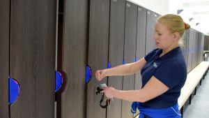 Nainen testaa uimahallin pukukoppien elektronista lukitusta
