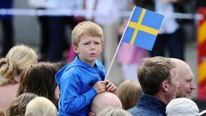 Ruotsin lippua heiluttava pikkupoika isänsä harteilla väkijoukossa.