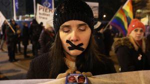 Mielenosoituksessa nainen, jonka suu teipattu mustalla teipillä