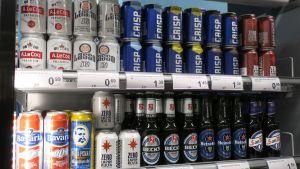 Alkoholittoman oluen tölkkejä ja pulloja kaupan kylmäkaapissa.
