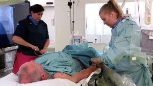 Kaksi hoitajaa valmistelee potilasta varjoainekuvaukseen.