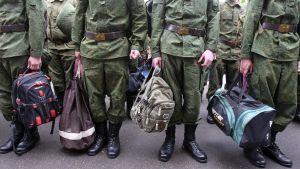 Joukko uusia varusmiehiä seisoo rivissä armeijan univormuissa, käsissään siviilireppuja ja laukkuja. Kuva on rajattu niin, että varusmiesten kasvoja ei näy.