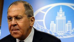 Etualalla kuvan vasemmassa laidassa on vakavailmeinen Sergei Lavrov tummassa puvussa. Taustalla näkyy sinisellä pohjalla Venäjän ulkoministeriön logo, johon on kuvattu ministeriön rakennus.