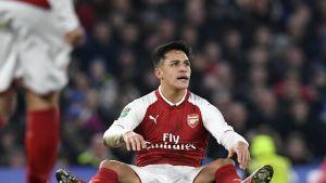 Alexis Sanchez istuu nurmen pinnassa.