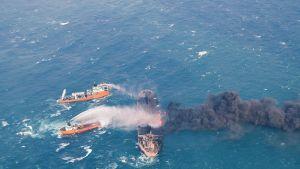 Säiliöalus palaa keskellä merta. Ympärillä kaksi muuta laivaa, jotka pyrkivät sammuttamaan riehuvia liekkejä.