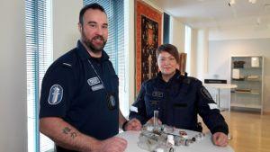 Poliisit pöydän ääressä, pöydällä huumeiden käyttöön liittyvää takavarikoitua materiaalia