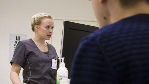 Sairaanhoitaja Teija Hietala valmistelee PerusTerveyden potilasta lääkärin vastaanotolle.