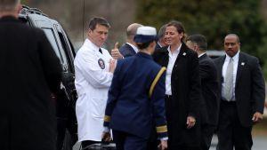 Ronny Jackson seisoo valkoisessa lääkärintakissa mustaa autoa vasten kädet ristissä, katsoo kameraan ja nostaa peukaloa. Ympärillä parveilee muuta Valkoisen talon henkilökuntaa.