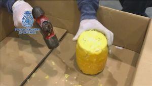 Kuvassa ananaksen sisälle kätkettyä kokaiinia, jonka päällä keltainen vahakalvo. Ihmisen kädet, joista toinen pitää kiinni kappaleesta ja toisessa kädessä on vasara.