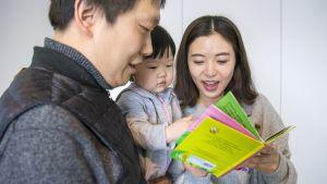 Isä Hakhyun Kim, äiti Dami Park ja Seo Woo -vauva tutkivat lastenkirjaa.