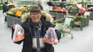 Hannele Kaskinen pitelee kahta hedelmäpussia kaupassa.