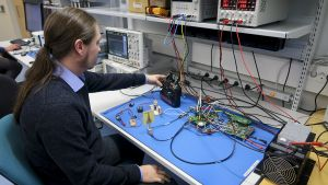 Palmikköpäinen nuori mies teknisten laitteiden äärellä.
