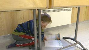 Poika lukee kirjaa pulpetin alla